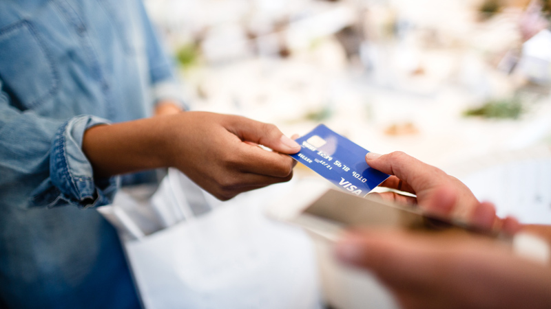 A Visa card being handed to a salesperson in a retail store