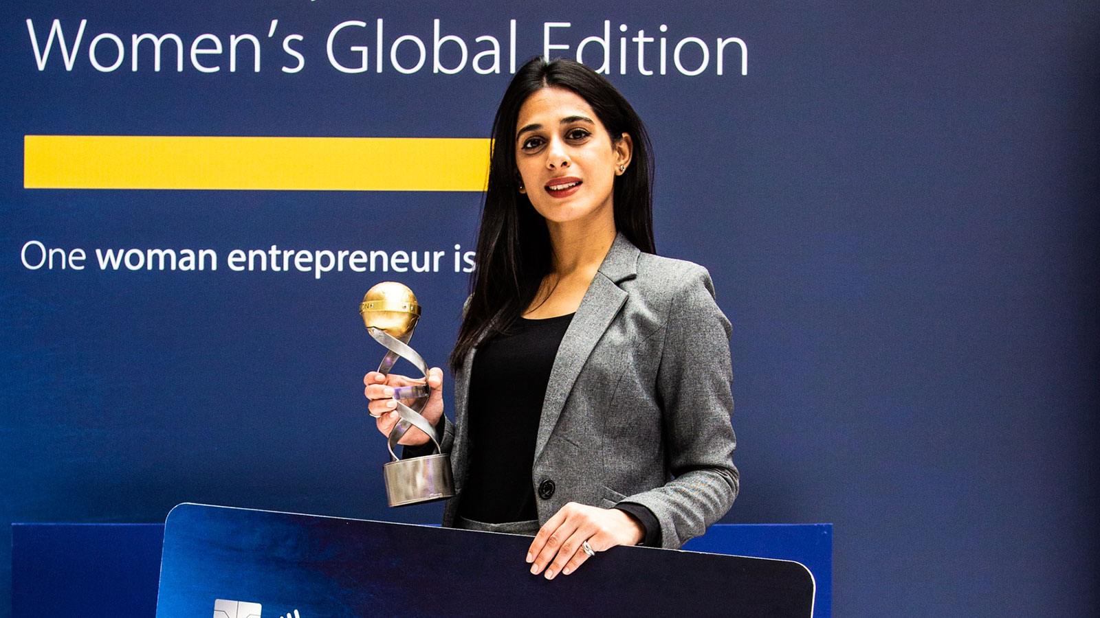 Naureen Hyat, winner of the Fintech challenge, posing with a trophy.